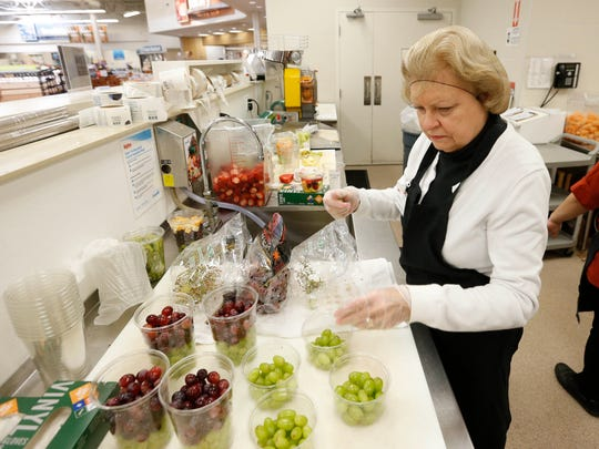 Mary Knueven puts together containers of grapes for sale Tuesday, March 15, 2016 at the Hy-Vee in Urbandale.