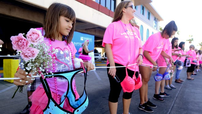 Avery Baudan prepares for the walk over the Bob Sikes Bridge during the 2016 Bras Across the Bridge walk. The new bras will be donated to local organizations that help women and girls in need.