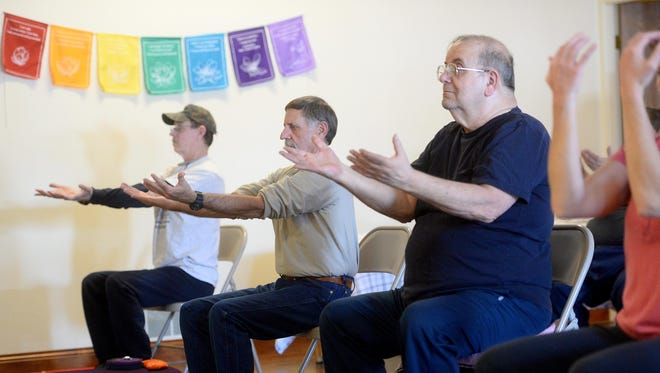 """Jim Pruitt, center, has found relief for chronic pain and PTSD symptoms through yoga. """"My overall well-being has improved since I started to yoga. It's truly a great tool,"""" he said."""