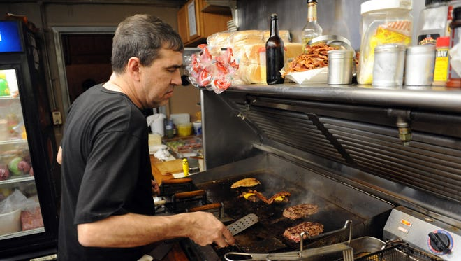 Owner Kenny Willey prepares food for customers at Olde Falls Inn on Newark Road. The restaurant has been under Willey's ownership for 15 years and is known for its ribs.