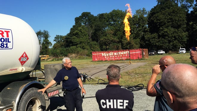 Instructor Kerry Fitzgerald discusses propane safety with first responders during a demonstration Tuesday at the state fire academy in Montour Falls. A propane flare burns in the background.