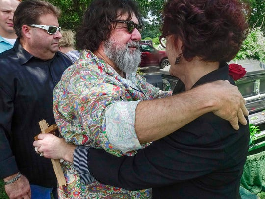 Musician Wayne Toups hugs Brenella Richard, widow of