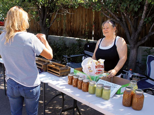 Bill Armendariz — Headlight Photo   Angie Mariscal, right, sold canned salsa and chile sauces she makes at home from a guarded family recipe. She also sold wood art by her husband during Saturday's Deming MainStreet Farmer's Market grand opening at the corner parking lot behind Mimbres Internal Medicine (the Mahoney Building). The Mariscal's were set up for the first time at the Farmer's Market and said they would return to sell their wares.