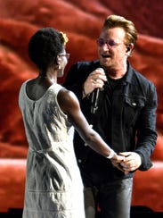 U2 lead singer Bono sings to an audience member during