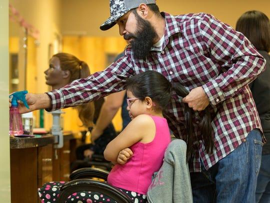 Ramon Lara braids the hair of his his daughter Leilanni