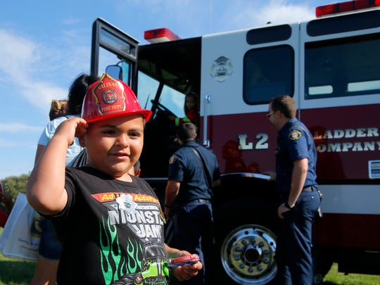 Jason Martinez, 4, tries on his new fire hat during the National Night Out celebration in Salinas on Tuesday.