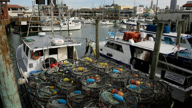File - In this Nov. 5, 2015 file photo, a fishing boat sits loaded with crab pots waiting to go out at Fisherman's Wharf in San Francisco. The wharf typically bustles this time of year as dozens of crab fisherman prepare to haul millions of pounds of Dungeness crab that are a tradition at Thanksgiving and other holiday meals. But crab pots are sitting empty on docks, boats are idled and fishermen are anxiously waiting for authorities to open the lucrative Dungeness crab season. (AP Photo/Eric Risberg, File)