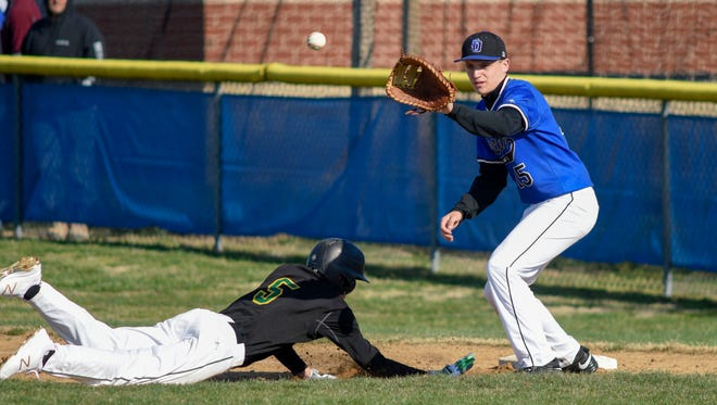 Queen Anne's Camden Lancaster safely dives back into first as Decatur's Tristan McDonough reaches for the ball during play at Stephen Decatur High School Tuesday afternoon in Berlin.