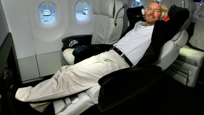 Sir Richard Branson, chairman of Virgin Group, relaxes in a first-class seat on a Virgin America Airbus A319 at Logan International Airport in Boston on, Feb. 11, 2009. It market an event for Virgin America's first non-stop flights from Boston to San Francisco and Los Angeles.