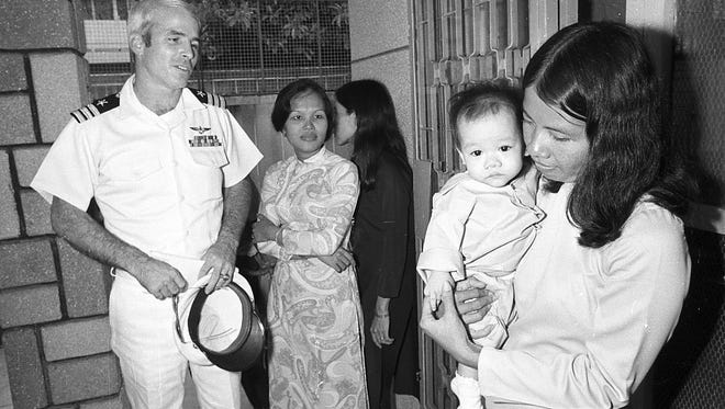 U.S. Navy Cmdr. John S. McCain III, a guest of the South Vietnamese government, visits the Holt orphanage in Saigon, Vietnam, on Oct. 30, 1974. The institution cares for many youngsters fathered by American GIs. McCain, son of the admiral who commanded U.S. forces in the Pacific at the height of the Vietnam War, was shot down over Hanoi and spent several years as a POW.
