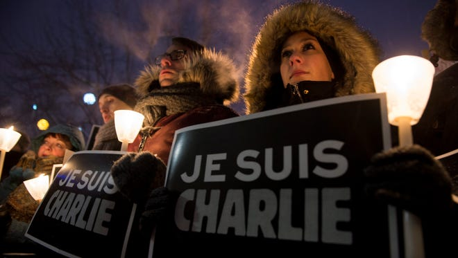 "People stand in front of City Hall with a sign that reads in French ""I am Charlie"" in solidarity with those killed in an attack at the Paris offices of the weekly newspaper ""Charlie Hebdo"" during a vigil on Jan. 7, 2015 in Montreal."