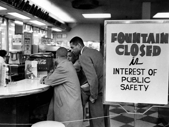 Student sit-in leader Rodney Powell, standing, talks with two of his companions after the lunch counter at a  Nashville Walgreens was closed on March 25, 1960, when the sit-ins started.