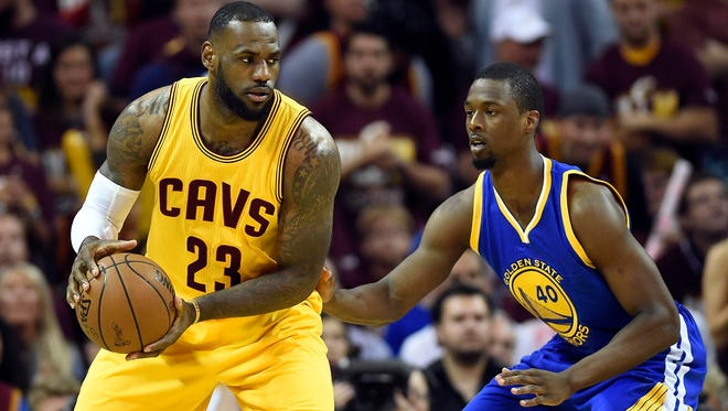 Cleveland Cavaliers forward LeBron James (23) handles the ball against Golden State Warriors forward Harrison Barnes (40) during the first quarter in game three of the NBA Finals at Quicken Loans Arena.