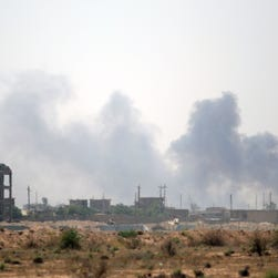 Smoke rises from buildings in Fallujah as members of the Iraqi government forces clear the streets of roadside bombs and booby traps  June 23, 2016.