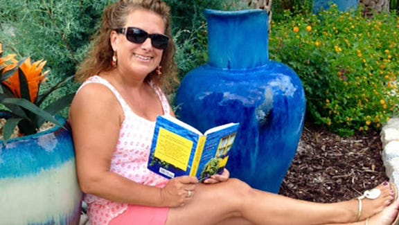 Jody Ryan reading her new book by the poolside.