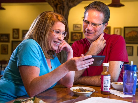 Rancho Pinot servers Jillian Coghill and Roger Brandt look at photos as they enjoy a meal of fried rice with beef, pork and shrimp that was cooked up for the staff of Rancho Pinot in Scottsdale, Friday, Nov. 11, 2016.