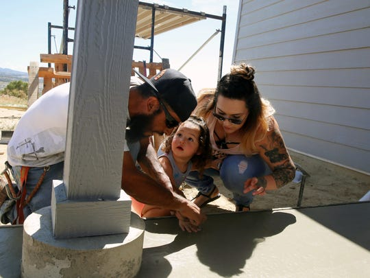 Gerald Herrera, left, and Hailey Tafoya help place Lena Tafoya's handprint into the concrete of the patio at the family's under-construction home on County Road 31190 on Friday.