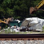 Workers pick up trash that busted from a sanitation truck after being hit  by a Norfolk Southern engine on Jude Brewer Road in Lumberton Thursday.
