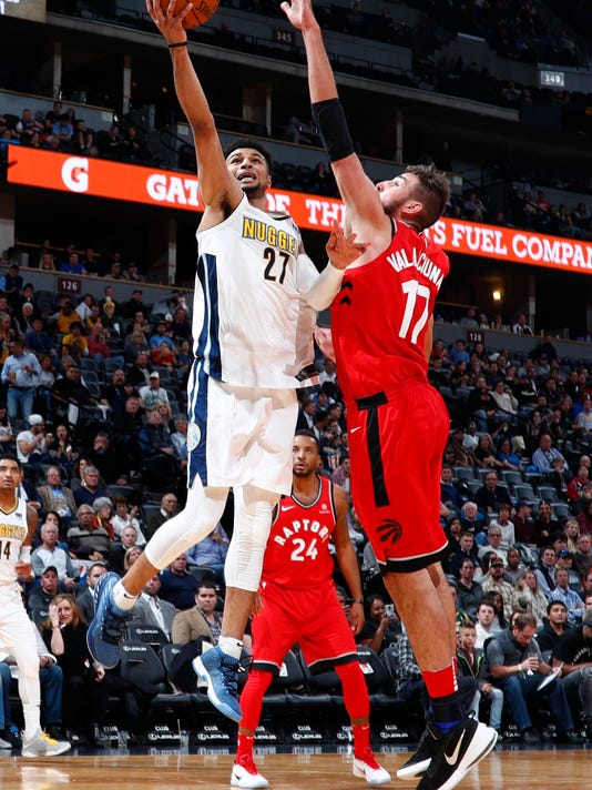 Denver Nuggets guard Jamal Murray, left, goes up for a basket as Toronto Raptors center Jonas Valanciunas. of Lithuania, defends in the second half of an NBA basketball game Wednesday, Nov. 1, 2017, in Denver. The Nuggets won 129-111. (AP Photo/David Zalubowski)