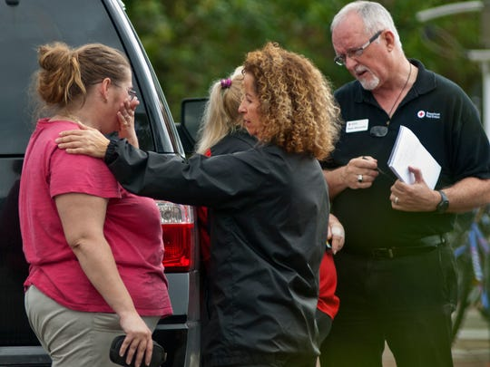 Kristy Phillips is comforted by representatives of local Red Cross at the scene of a fire in Bonita Springs that cvlaimed the life of her grandmother, Shirley Corrigan.