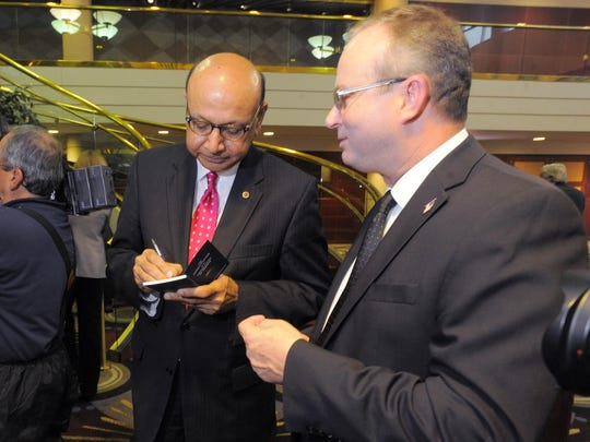 Khizr Khan autographs a copy of the U.S. Constitution for 19th District Judge Mark Sommers.