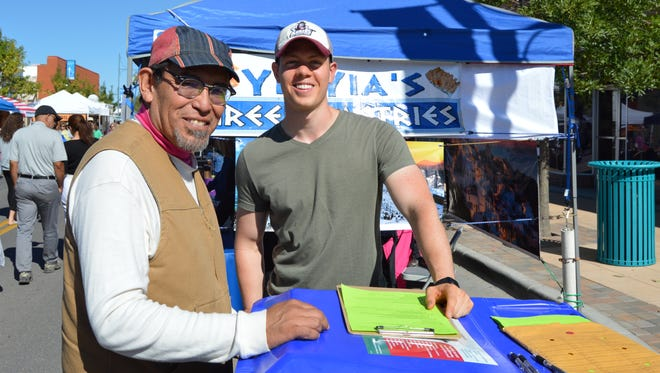 Former Las Cruces City Councilor Miguel Silva, left, stands with OASIS student Bryan Murphy while taking the 2015 South Central Solid Waste Authority Recycling Survey at the Las Cruces Farmers and Crafts Market.