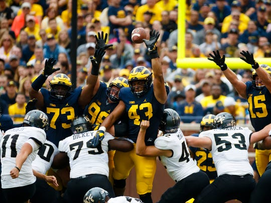 Sep 10, 2016; Ann Arbor, MI, USA; Michigan Wolverines defensive tackle Maurice Hurst (73) and defensive end Chris Wormley (43) block a field goal attempt by UCF Knights place kicker Matthew Wright (11) in the second quarter at Michigan Stadium.