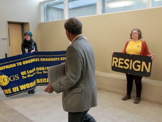 University of Iowa President Bruce Harreld greets protesters