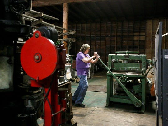 Ardis Birch demonstrates how to use a large paper cutter left in the storage area of an Oregon Fruit Products warehouse on Thursday, July 6, 2017, in Salem, Ore. Birch is the unofficial historian for the company, able to recount old layouts of the plant and uses of now-defunct equipment.