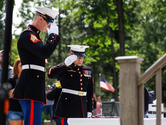 Cena's handlers Jon North, left, and Jeffrey DeYoung, right, salute to Cena's urn during the memorial service at the Michigan War Dog Memorial in Lyon Township, Saturday, August 26, 2017.