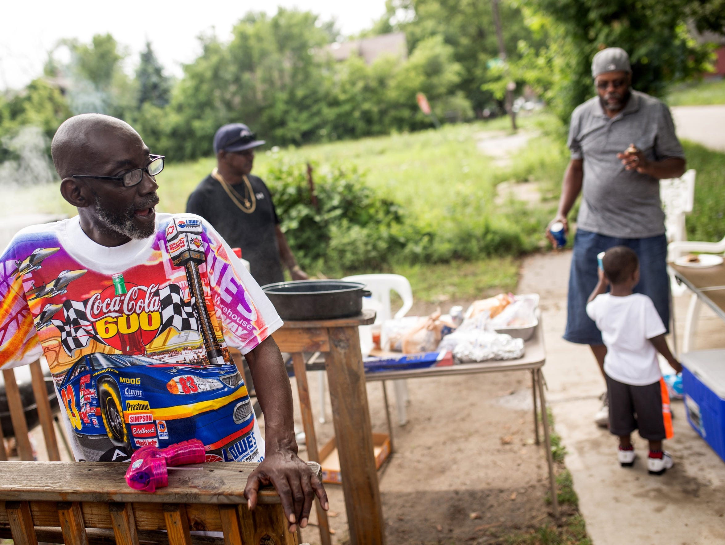 """Everybody's related,"" Jeffrey Robinson, 64, left, said about his Vanderbilt Street neighbors during a family cookout in Detroit's Delray neighborhood on July 12, 2017."
