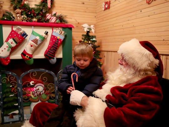 Santa gives a candy cane to Zayne Hurse, 4, of Salem,