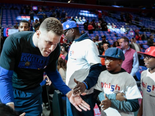 Blake Griffin high fives kids as he heads to the court before his Detroit Pistons debut against the Memphis Grizzlies at Little Caesars Arena on Thursday, Feb. 1, 2018.