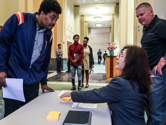 Ken Wilson Jr., 38, of Detroit signs in with Catherine King, Senior Vice President of Recruitment and Staffing services for Allied Universal Security Services at their hiring event at Greater Grace Temple in Detroit on Tuesday, May 15, 2018. General Manager Luke Gordley, 43, of Fenton looks on.