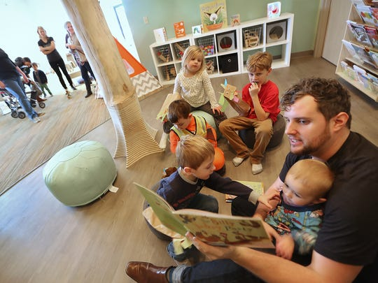 Craig Underwood reads to kids at the Urban Chalkboard, in Carmel, Tuesday, November 25, 2014.  The combination learning studio/cafe for children birth to six, and their parents, is due to open soon.  Parents can have coffee or tea while their kids play.  There will also be classes for parents and kids, like yoga.