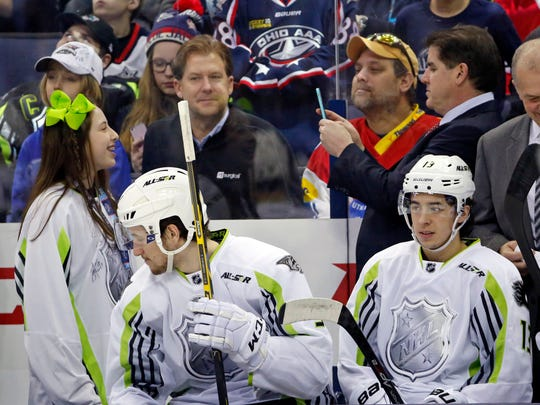 Team Toews coach Peter Laviolette of the Predators, second from right rear, takes a picture of his daughter, left, who joined him behind the bench during the first period of the All-Star game Sunday.