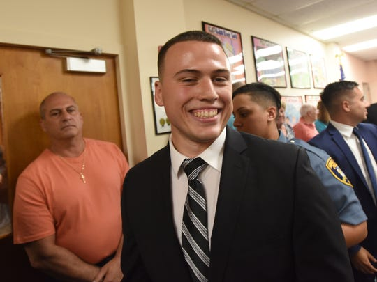 Joseph Camilleri Jr. was sworn in as a Saddle Brook police officer in July, and his father, Councilman Joseph Camilleri Sr., in orange T-shirt, had to resign because of an anti-nepotism ordinance.