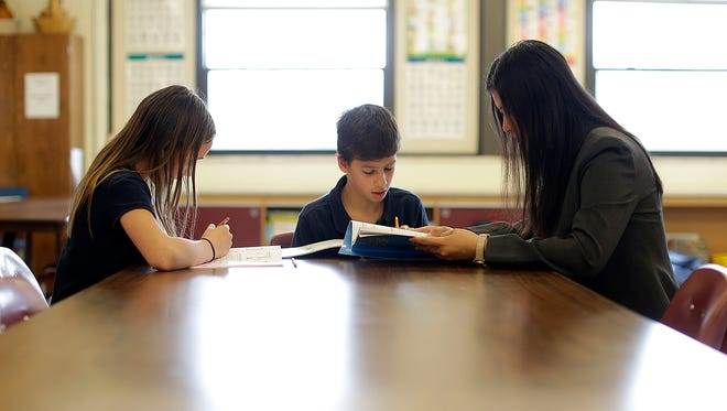 Matteo Dalessandro, middle, and Kate V., left, work with their Mandarin teacher Xuan Wang at Our Lady of Lourdes school in De Pere.