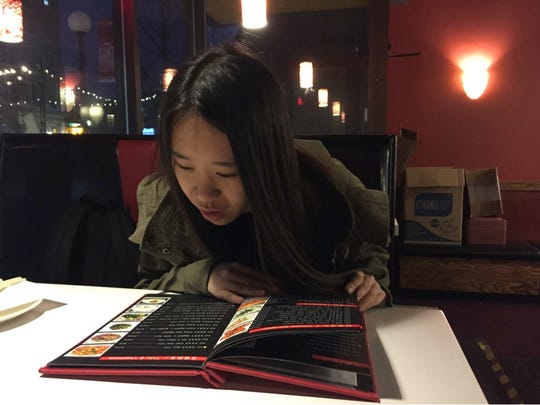 University of Iowa senior Jia Yuanfang, from Hebei, China and studying business and art, at Food Republic, a downtown Iowa City restaurant, in early December 2015.