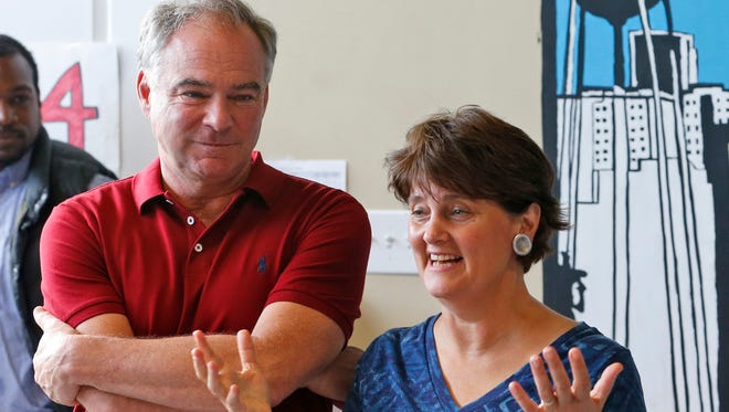 In this Aug. 1, 2016 photo, Democratic vice presidential candidate, Sen. Tim Kaine, D-Va., listens at left as his wife, Anne Holton speaks at a campaign office in Richmond, Va.