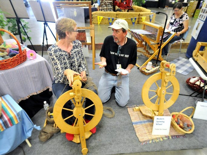 JOSEPH A. GARCIA/THE STAR Ventura County Star reporter Tom Kisken talks with Linda Price, of Camarillo, about using the spinning wheel at the Ventura County Fair.
