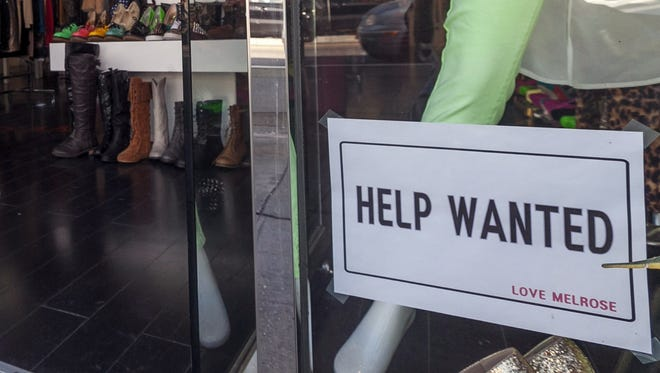In this  Friday, Dec. 7, 2012, photo, a help wanted sign is posted on the front window of a clothing boutique in Los Angeles.The number of Americans seeking unemployment benefits fell sharply for a fourth straight week, a sign that the job market may be improving. The Labor Department said Thursday, Dec. 13, 2012, that weekly applications for unemployment benefits fell 29,000 last week to a seasonally adjusted 343,000, the lowest in two months. It is the second-lowest total this year.  (AP Photo/Damian Dovarganes) ORG XMIT: NYBZ148
