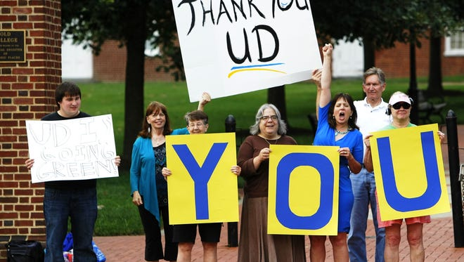 Amy Roe cheers with fellow supporters along Main Street in Newark on Thursday as they celebrate UD's decision to pull the plug on the data center.