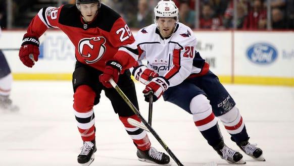 New Jersey Devils defenseman Damon Severson (28) competes