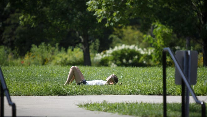 in this 2011 photo, Katie Shelander of Madeira relaxes in the sun and enjoys the nice weather in Ault Park during her lunch break. Brendon Cull writes in to back a property tax levy to support and improve the parks he loves.