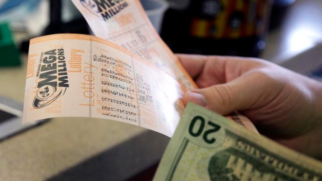Scott Hoormann holds two Mega Millions lottery tickets he purchased Monday at Energy Express in St. Louis.