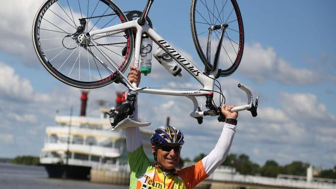 A rider raises his bike in celebration after reaching the Mississippi River and completing the final day of RAGBRAI XLI on July 27, 2013, in Fort Madison.