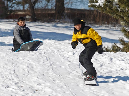 """We don't get much snow so we have to take advantage of it,"" says Freddy Ramirez as he and his son Jacob take a little time in the early morning to get in a few snowboard and sled runs in at Currie Park in Wauwatosa in 2012."