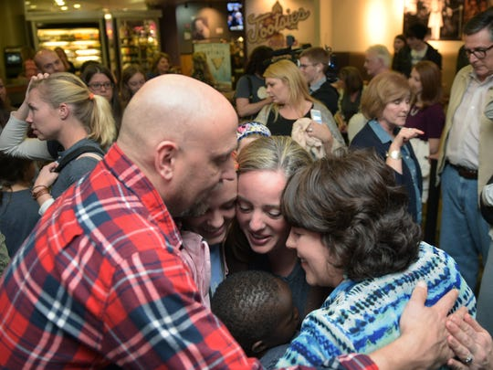 Family and friends embrace Julie Johnson, center, and her adopted son, Daniel, at Nashville International Airport on Friday. After several years of effort, Julie and Roger Johnson of Franklin finally brought home Daniel from the Democratic Republic of the Congo.