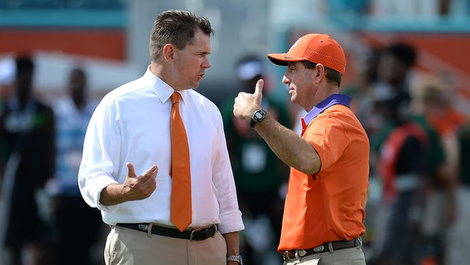 Clemson head coach Dabo Swinney talks with Miami head coach Al Golden before their game Saturday, Oct. 24, 2015, in Miami Gardens, Fla.